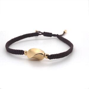 Armband zijde dark brown met sluing in 18 karaat geelgodu. Element 'twister' in 18 karaat geelgoud.